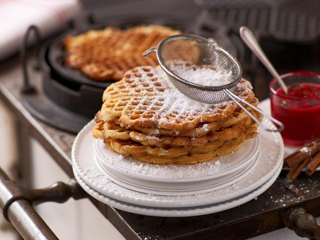 A sieve of icing sugar on top of a stack of cinnamon waffles