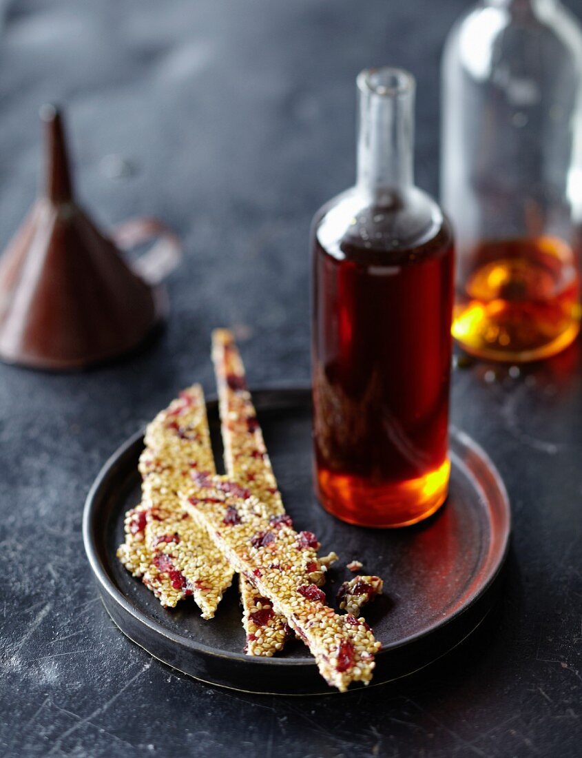 A bottle of caramel syrup and sesame brittle with cranberries