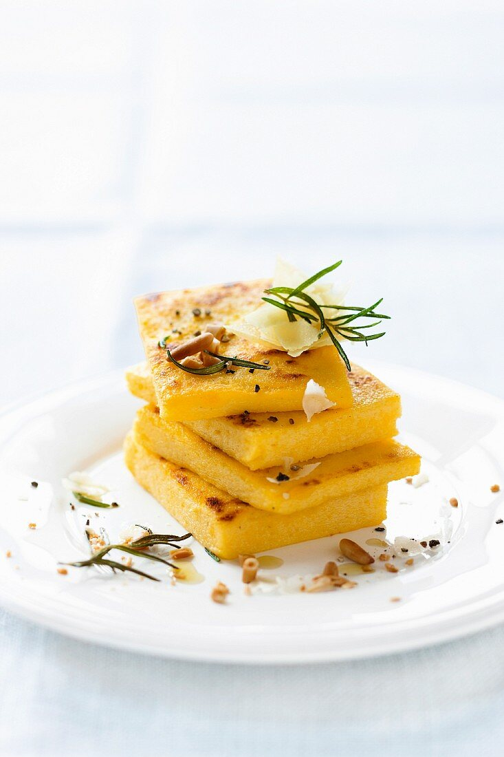 Polenta slices with pine nuts, rosemary and Parmesan