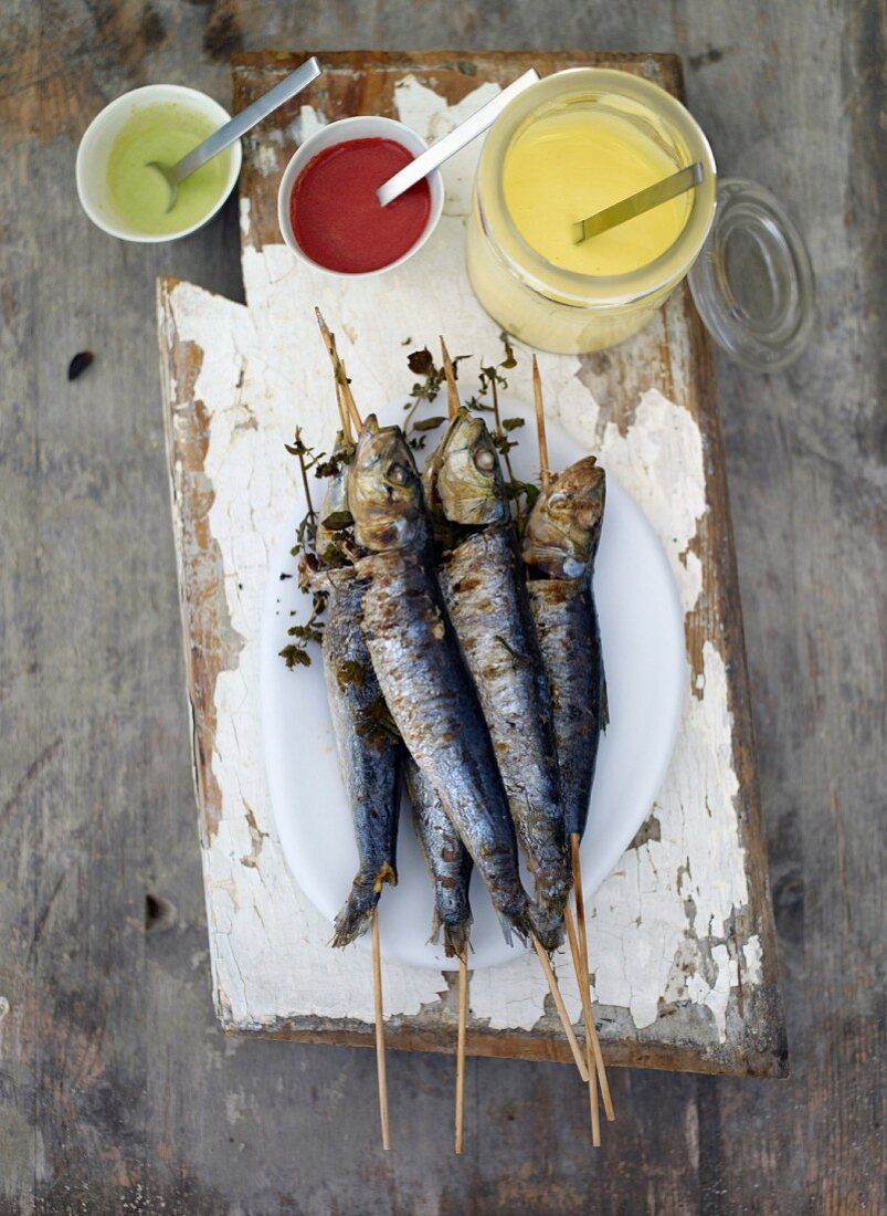Grilled sardines on sticks with various dips