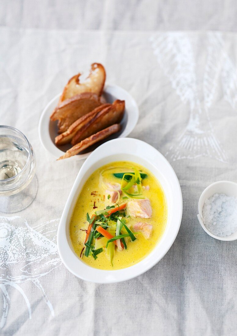 Saffron fish soup with vegetables and grilled bread