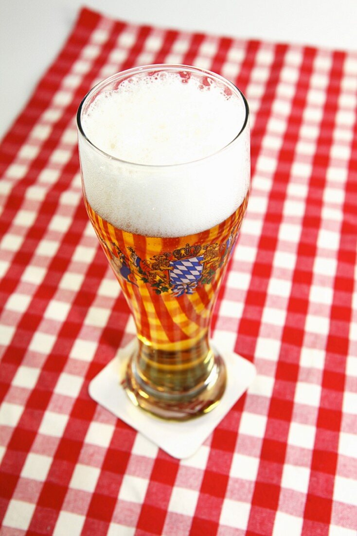 A glass of beer with a head of foam on a red and white checked tablecloth