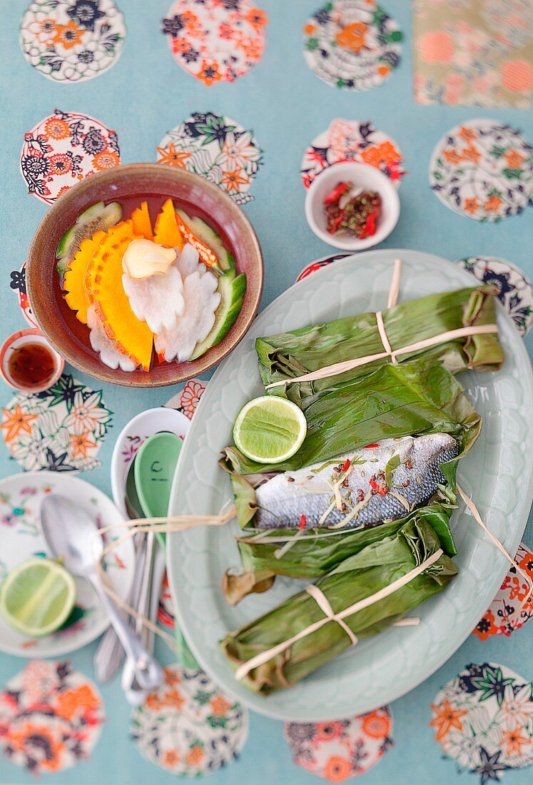 Sea bass cooked in banana leaves served with pickled vegetables (Vietnam)