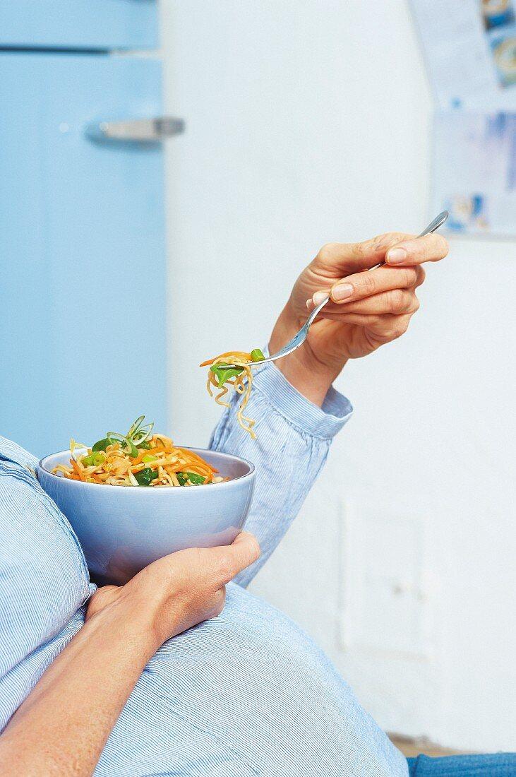 A pregnant woman eating a vegetarian stir-fry