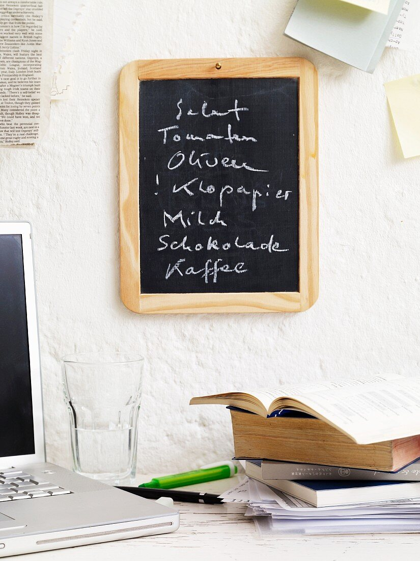 A laptop and books underneath a shopping list on a blackboard in a student apartment