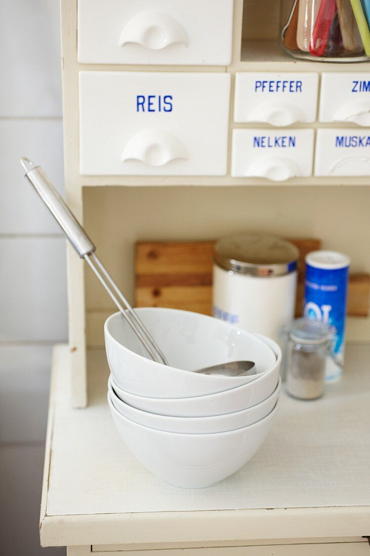 A stack of white bowls on a dresser in a student kitchen
