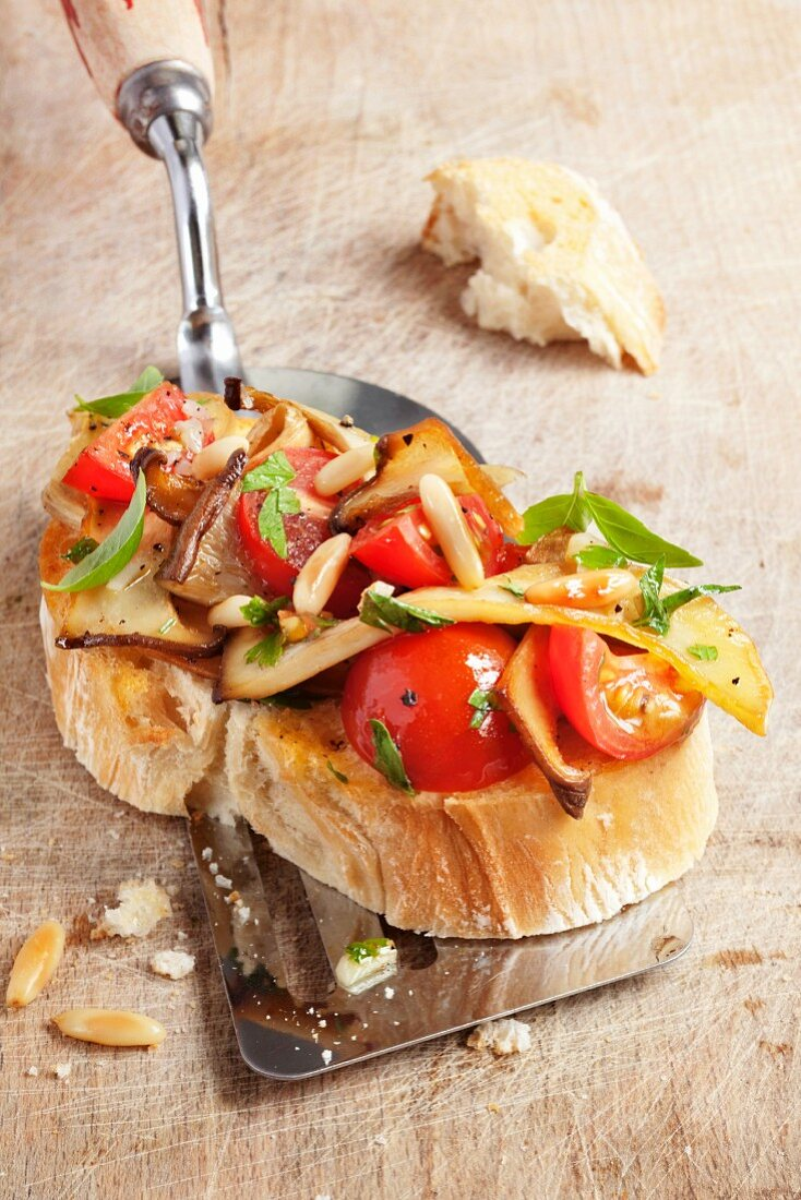 Bruschetta topped with king trumpet mushrooms on a spatula