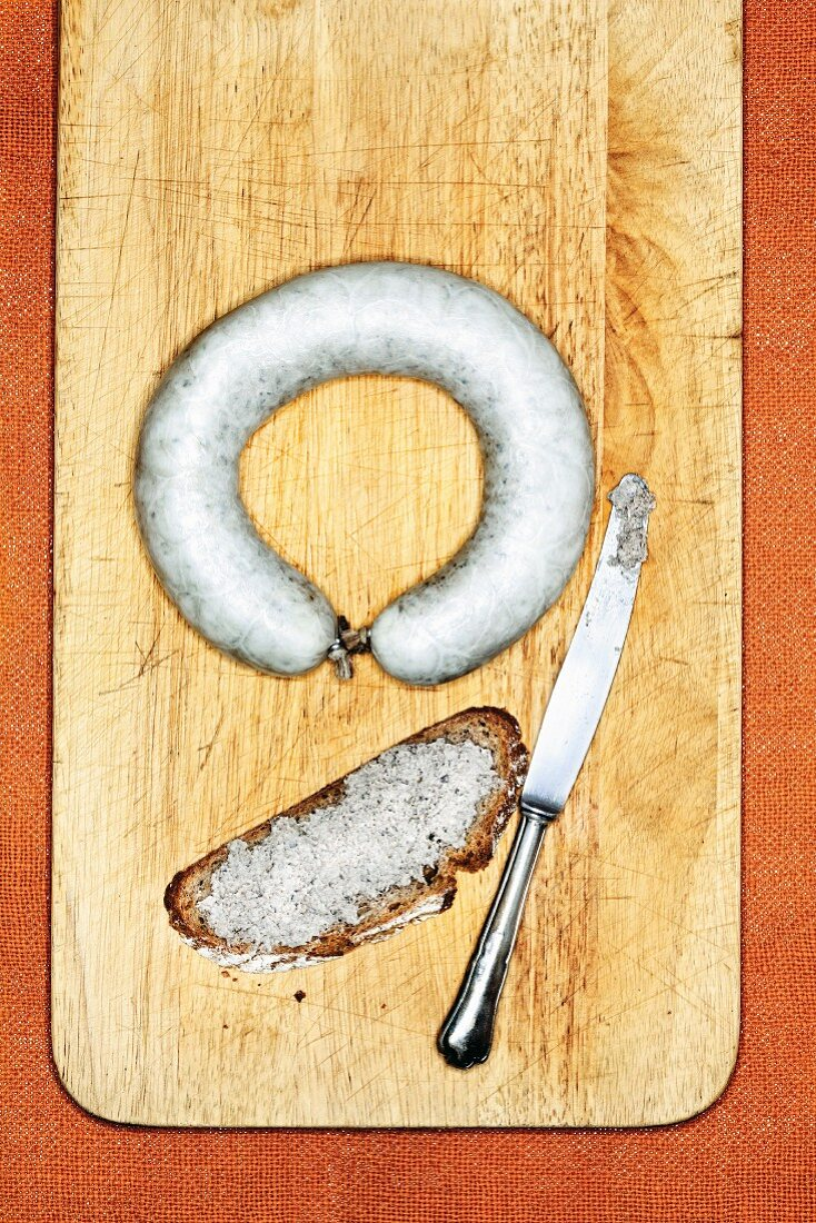 Palatinate liver sausage and a slice of bread spread with it on a wooden board with a knife (seen from above)