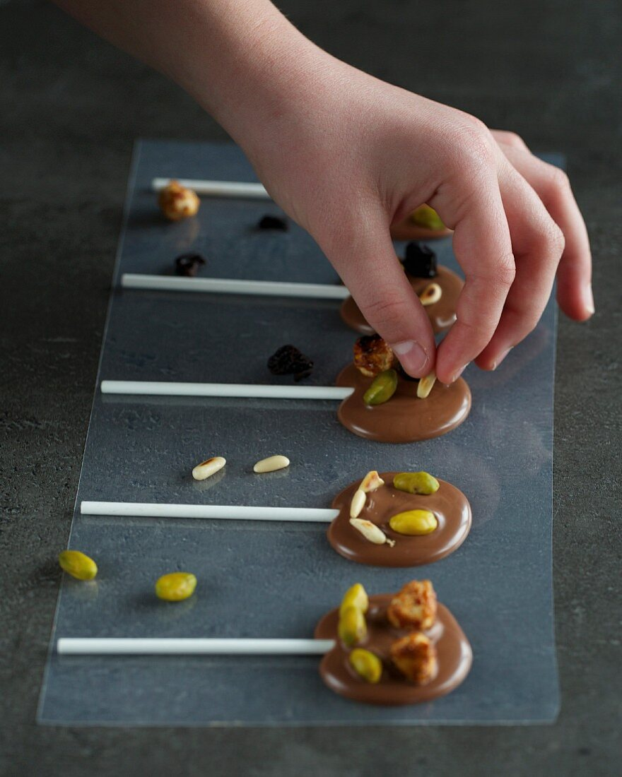 Chocolate lollies being decorated with pine nuts and pistachios