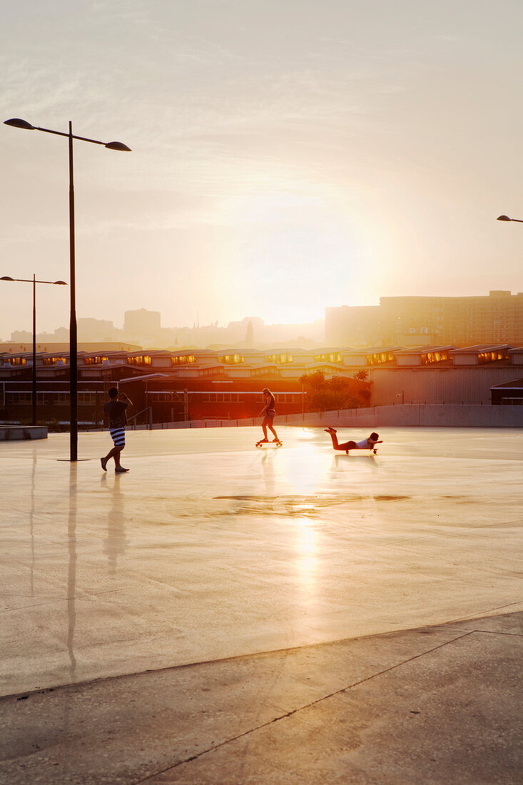 Children on skateboards at sunset in Durban, South Africa