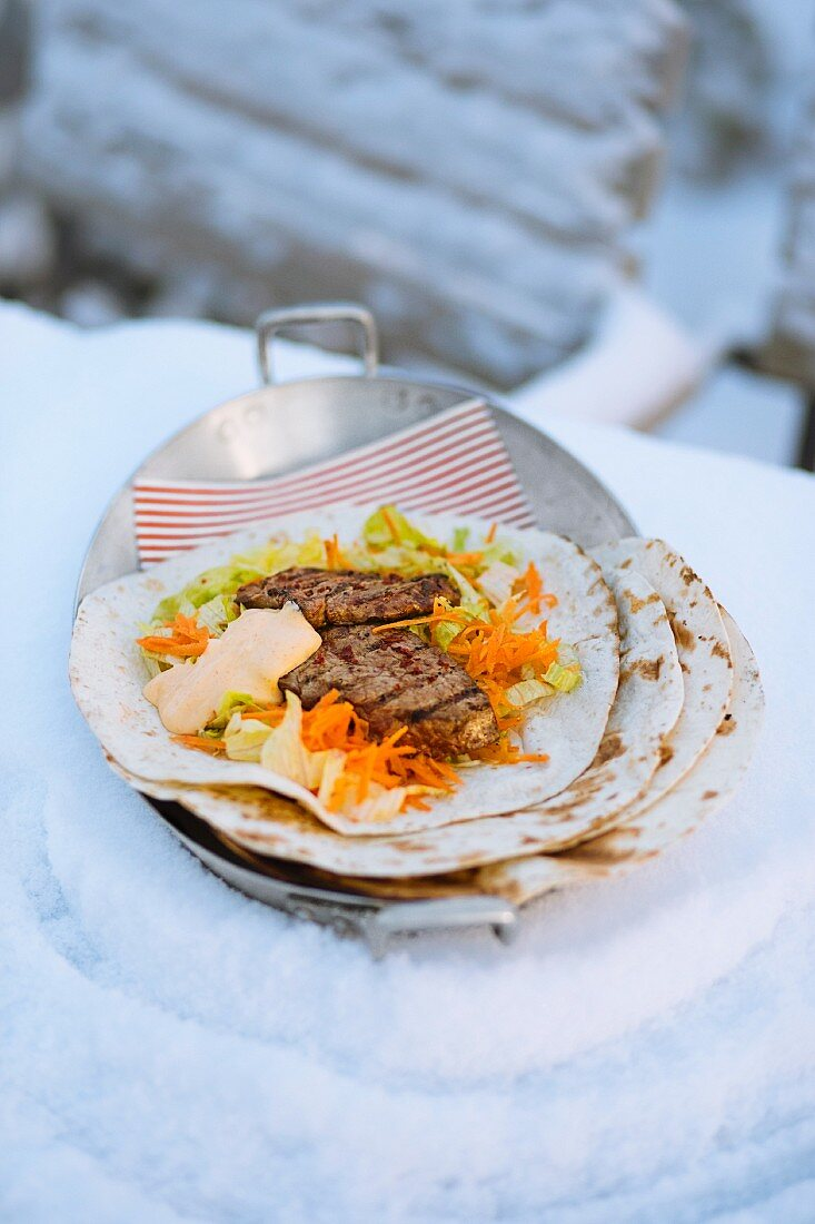 A steak wrap with a carrot and iceberg lettuce salad