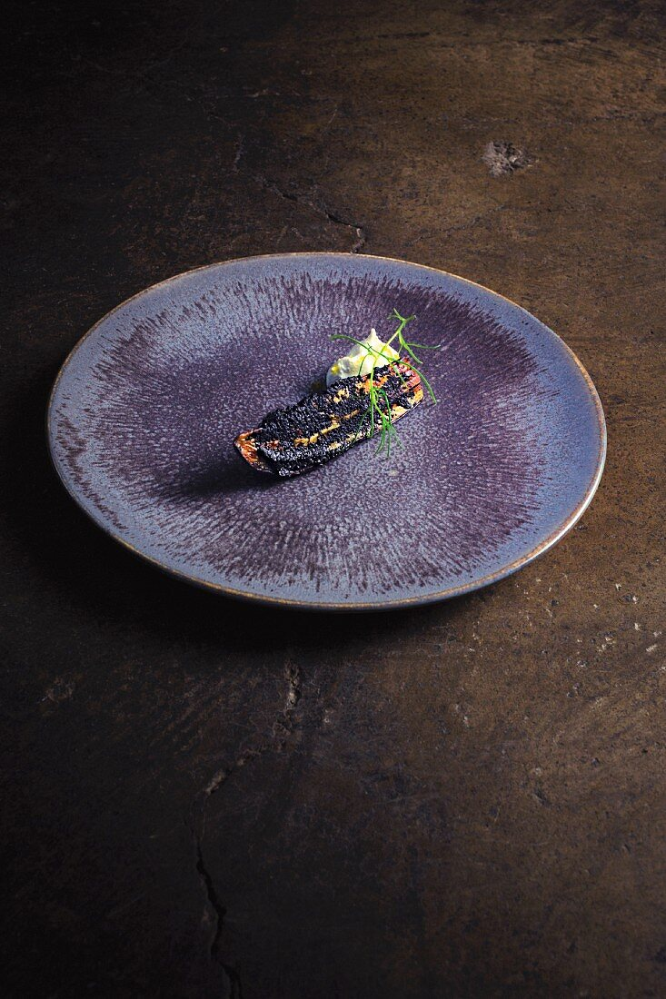 Grilled eggplant with black curry and sheep yogurt on plate