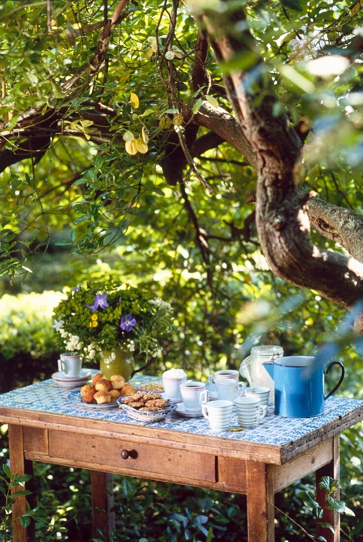 A rustic coffee table beneath a tree in a garden