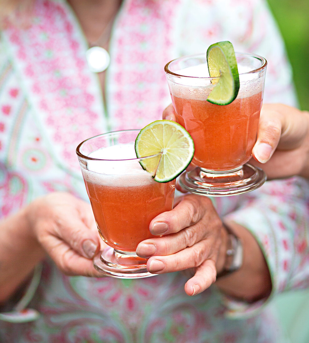 Two people toasting with Berry Spritz cocktails