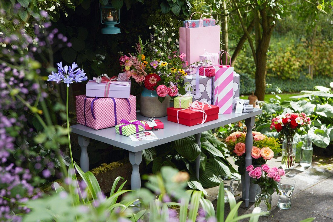 Gifts and a bunch of flowers on a table in a summery garden