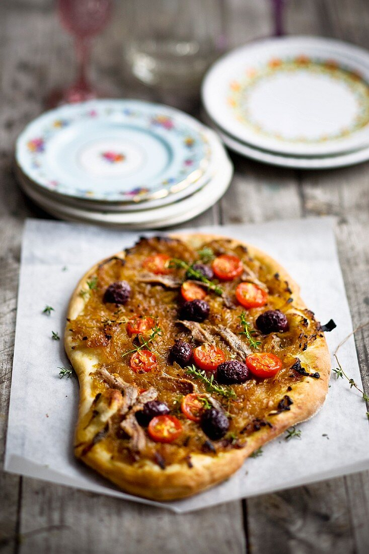 Pissaladiere with onions, sardines, olives and cherry tomatoes