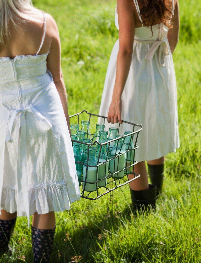 Girls in nostalgic summer dresses carrying several milk bottles in metal crate