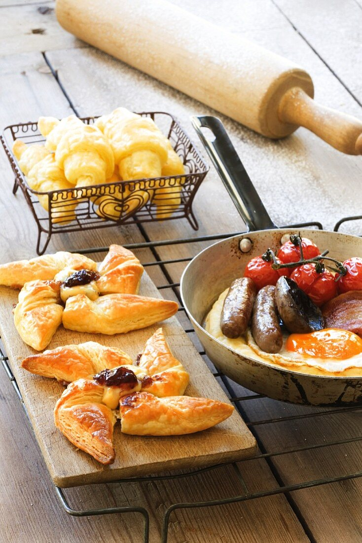 A breakfast of cheese croissants, sweet windmill pastries and puff pastry pizza topped with sausages and egg