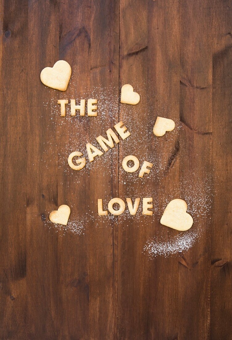 Letters made from biscuits, spelling out 'The Game of Love', with heart-shaped biscuits and sugar