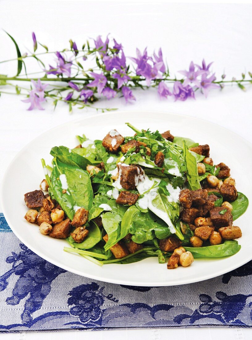 Salad of spinach with aubergines, chickpeas and a yoghurt dressing