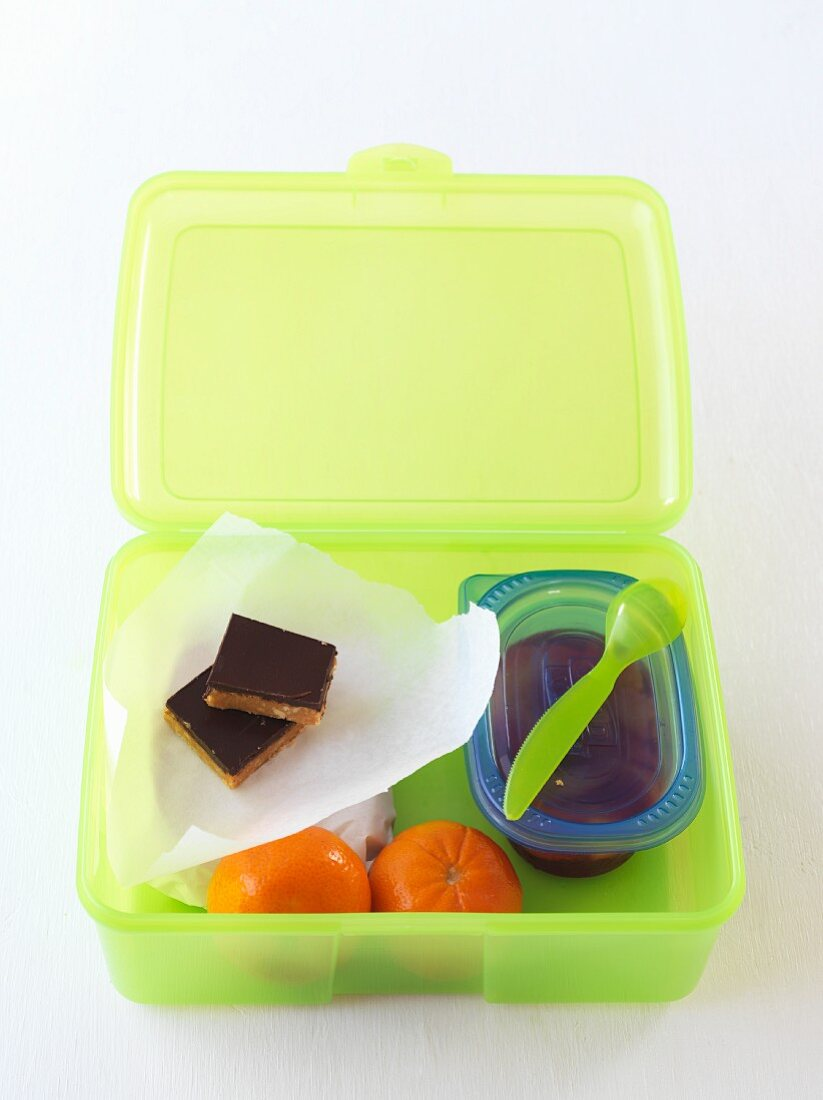 Chocolate cake and clementines in a lunchbox
