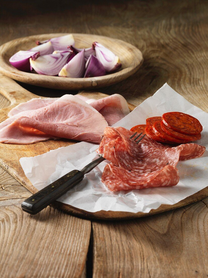 Sliced cured meats with red onion