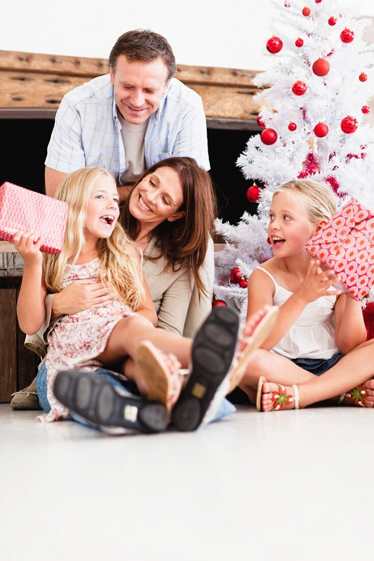 Girls shaking wrapped Christmas gifts