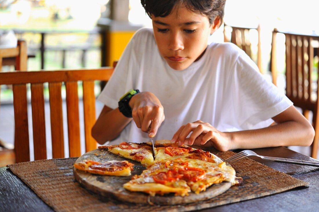 A boy slicing a pizza