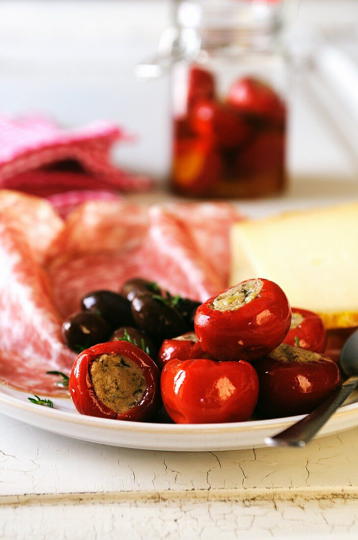 Antipasti platter with stuffed chilli peppers, olives, meat and cheese