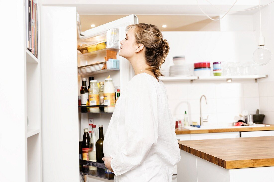 Pregnant woman searching fridge for food