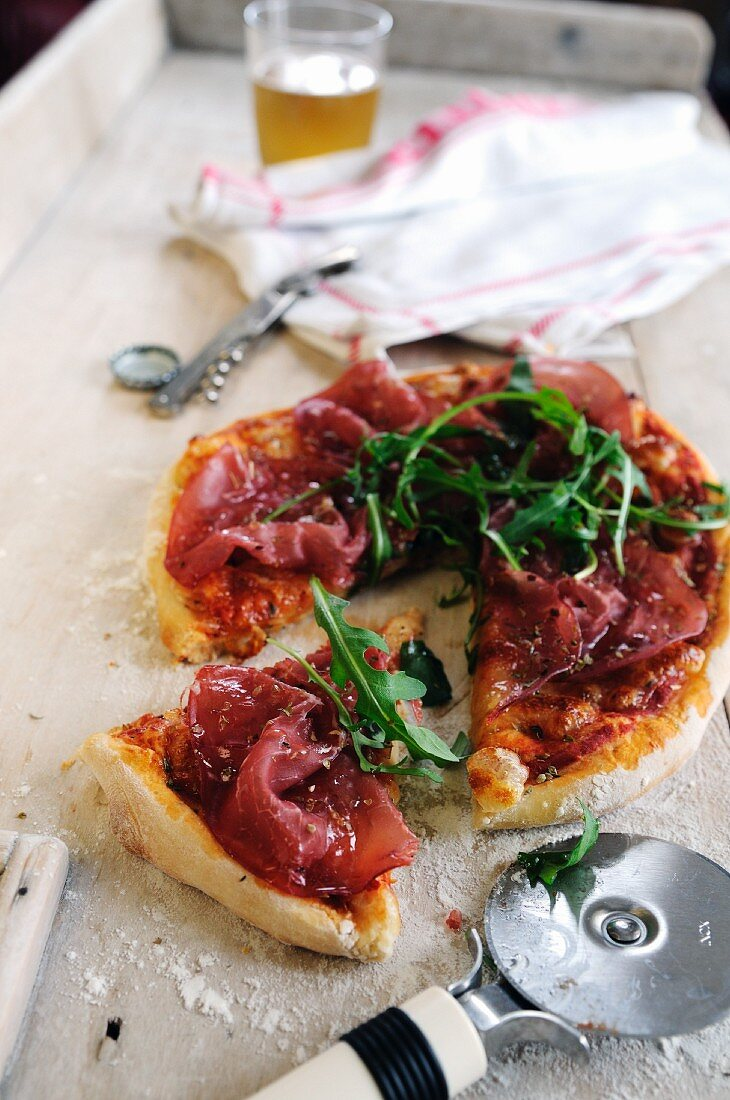Pizza topped with Bresaola and rocket leaves