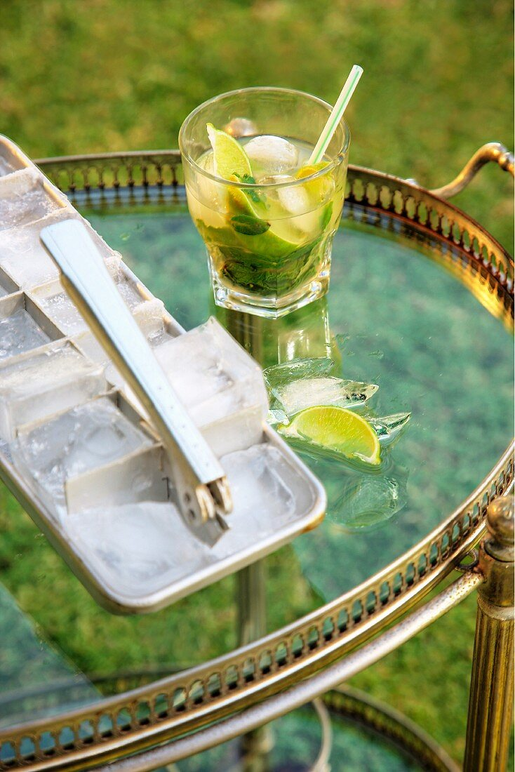 A mojito next to an ice cube tray and bar tongs on a tea trolley