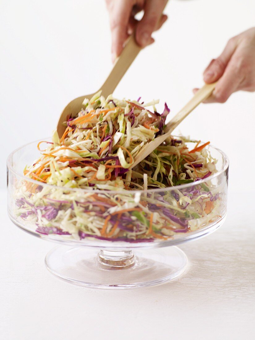Hands Tossing Cole Slaw in a Serving Bowl