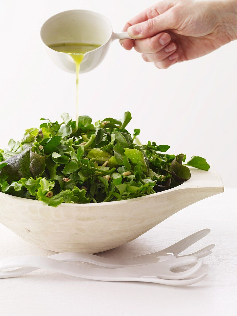 Hand Pouring Dressing Over Salad