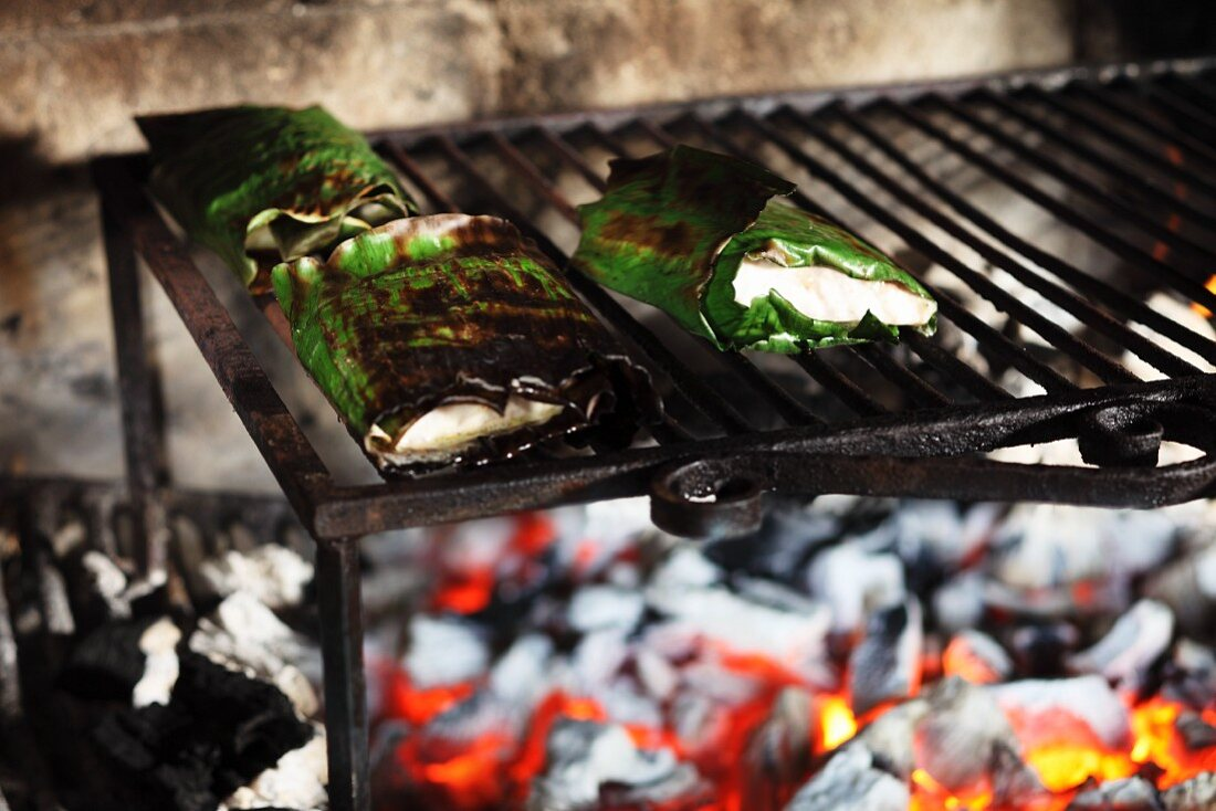 Sturgeon fillets wrapped in banana leaves on a wood-fired barbecue