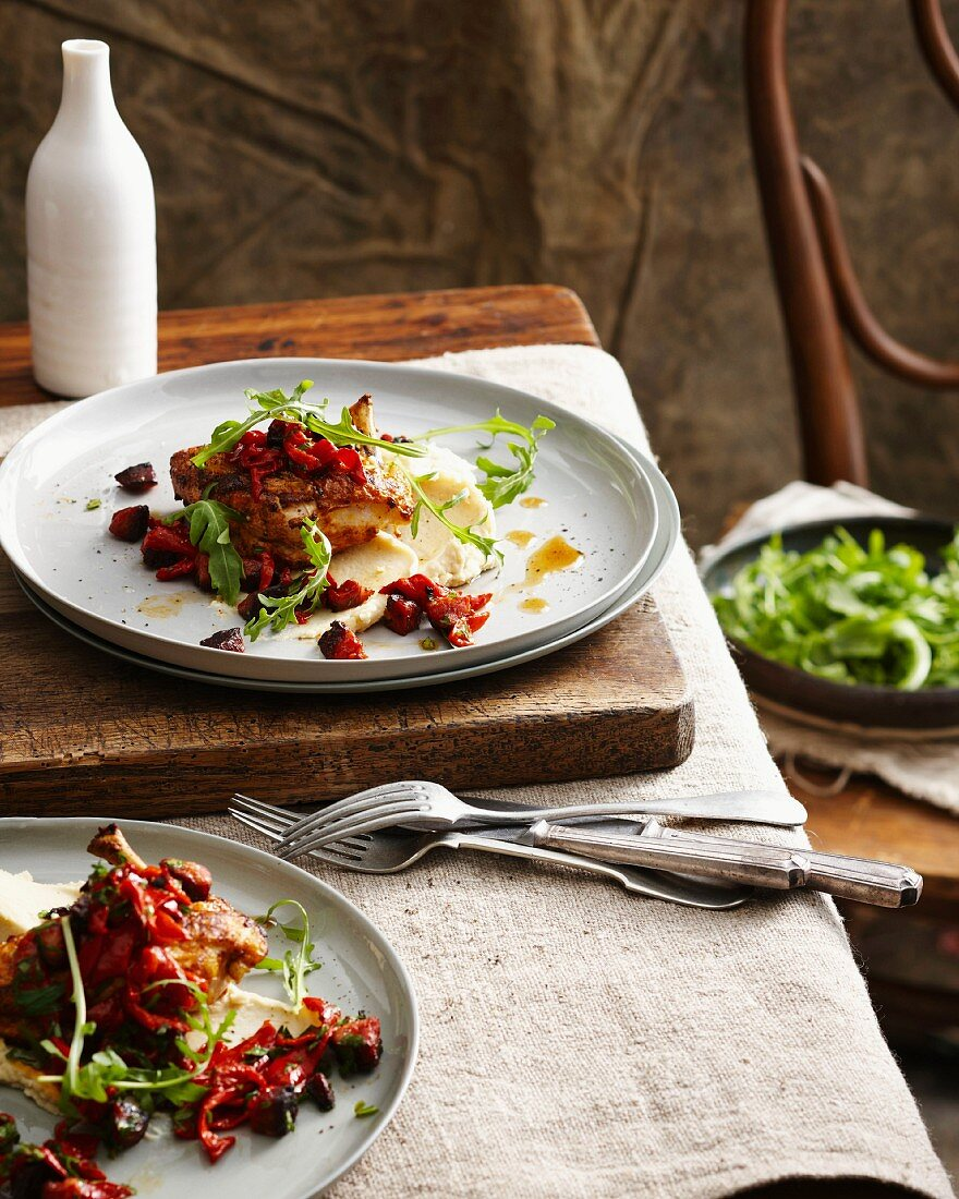 Plates of chicken with chorizo and salad