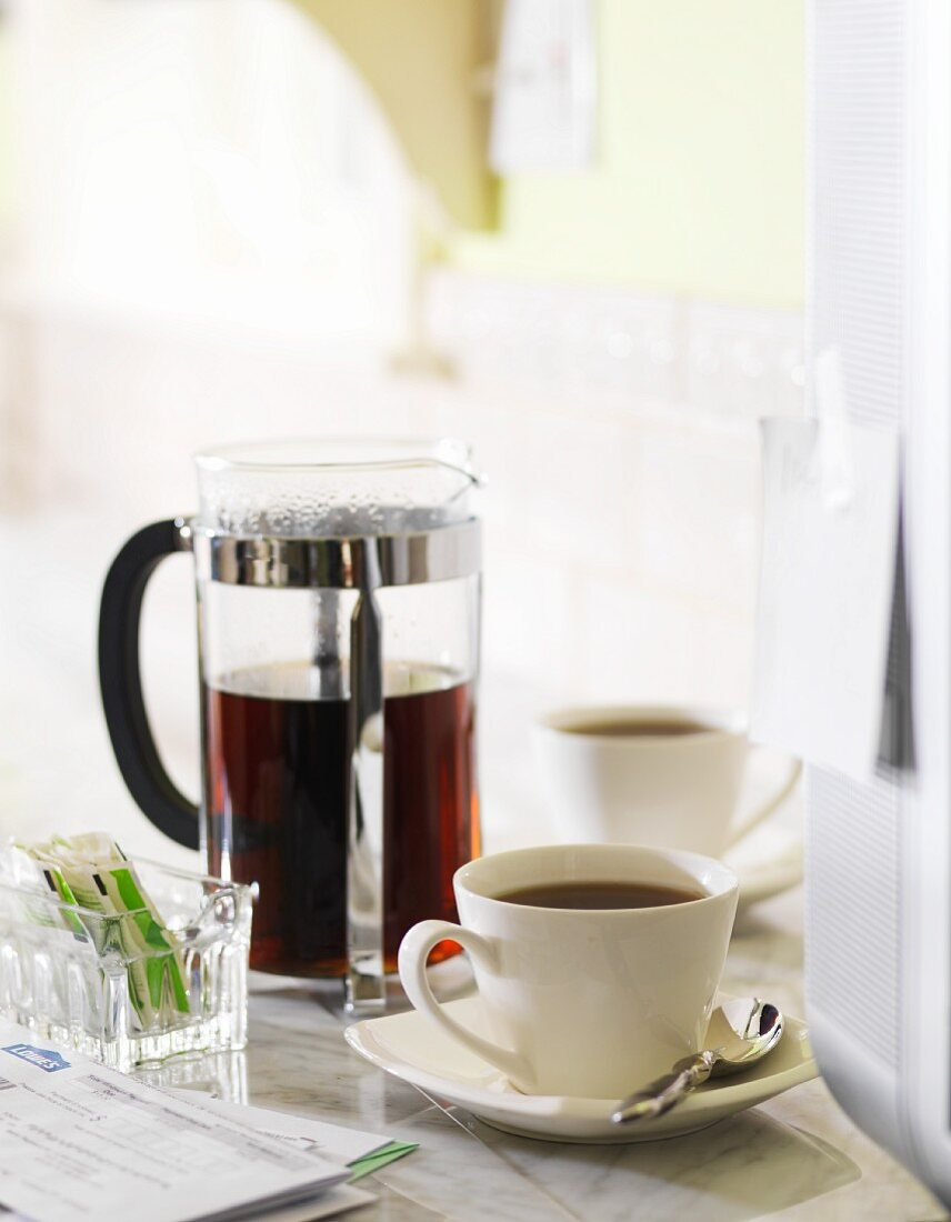 A Cup of Black Coffee Next to a French Press