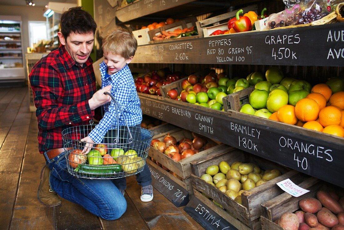 Father and son buying produce in store