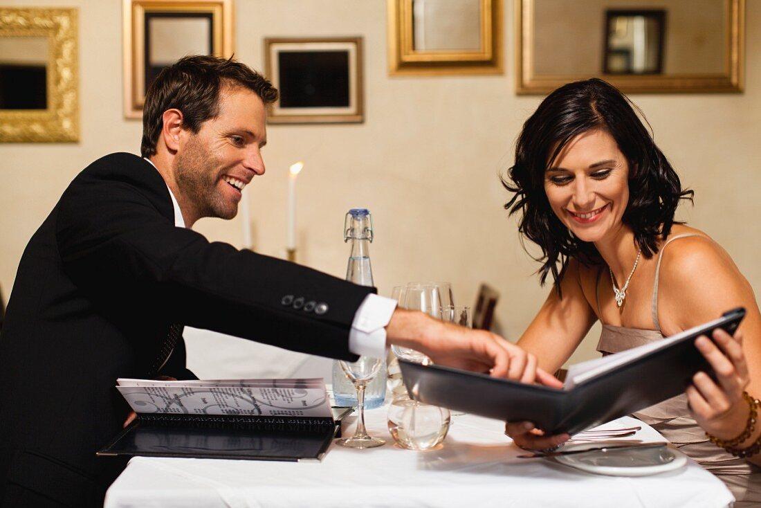 Paar beim Lesen der Speisekarte in einem Restaurant