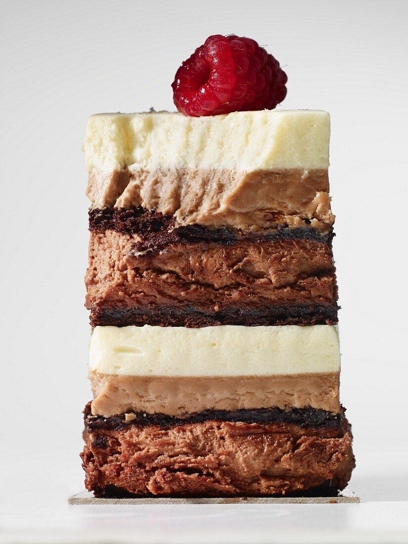 A slice of layered chocolate cake topped with a raspberry