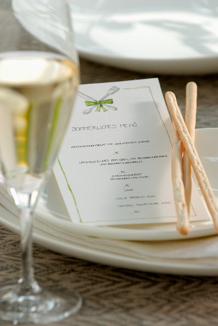 Breadsticks and a menu card on a plate next to a full wine glass