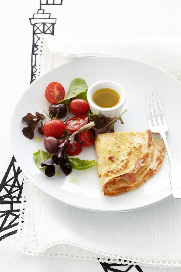 A savoury crepe filled with ham and served with a side salad
