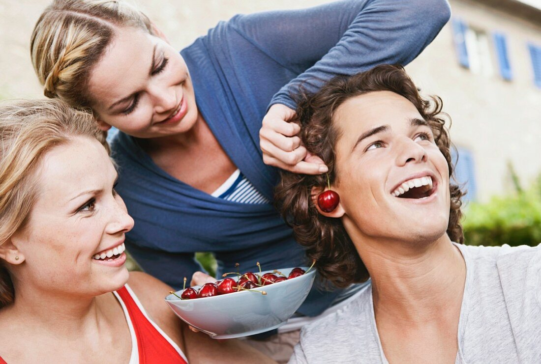 Two young women and a young man making cherry earrings