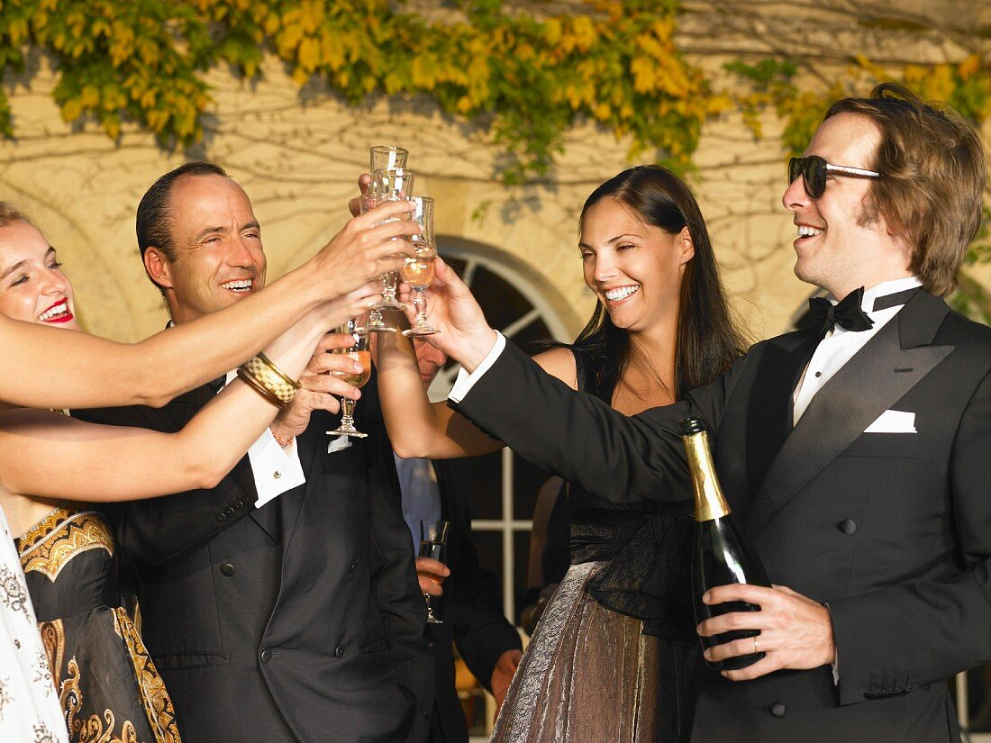 Menschen trinken Champagner bei Sonnenuntergang
