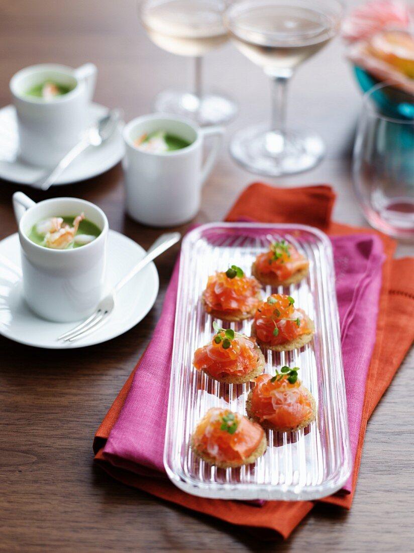 Salmon bites with keta caviar and cups of pea soup