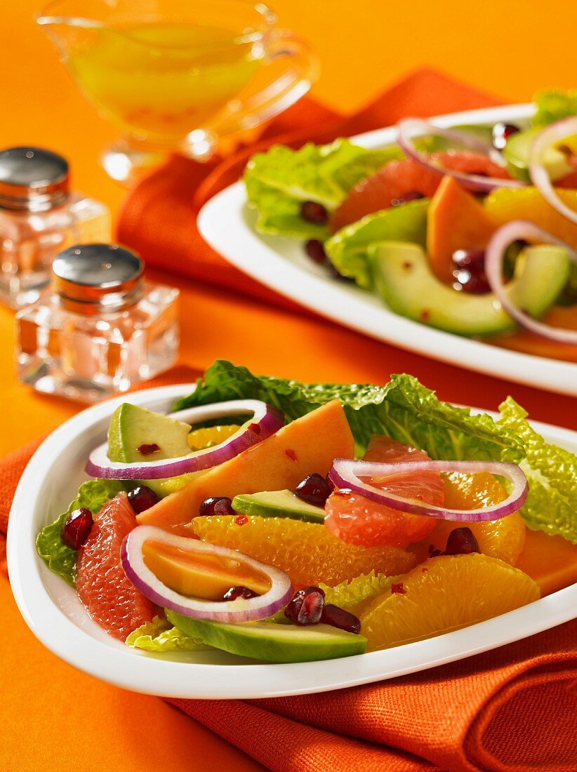 Citrus fruit salad with pomegranate seeds, avocado and red onions