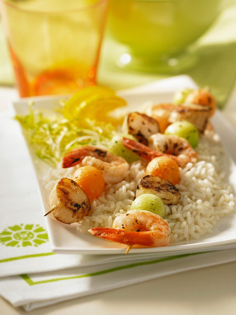 Grilled prawn and scallop kebabs with melon balls on a bed of rice