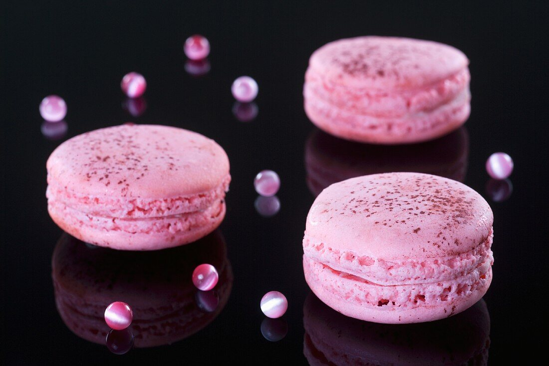 Pink macaroons on a shiny suface