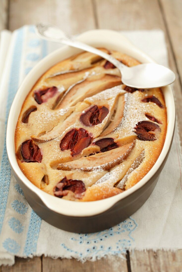 Pear and plum clafouti in a baking dish