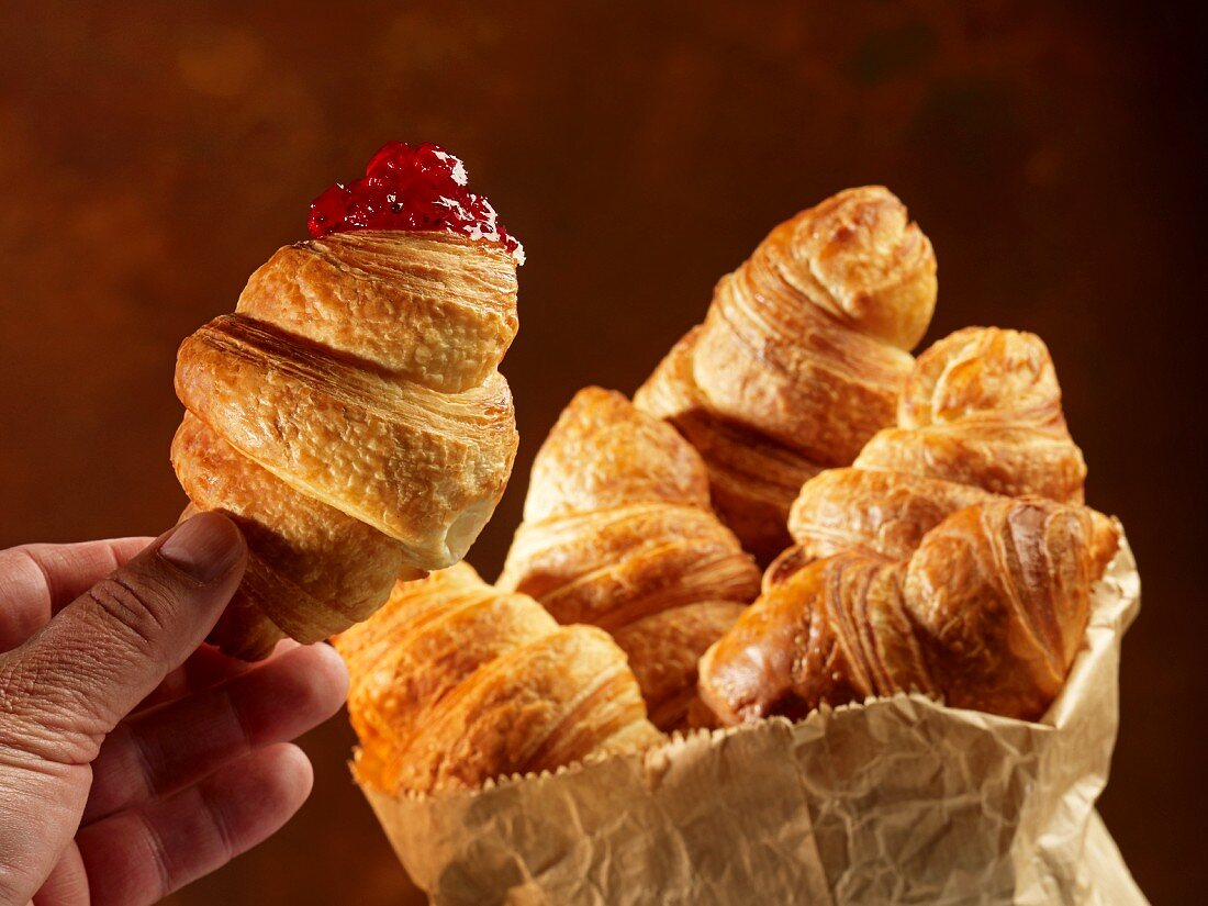Croissants in a paper bag and one in a hand with redcurrant jam